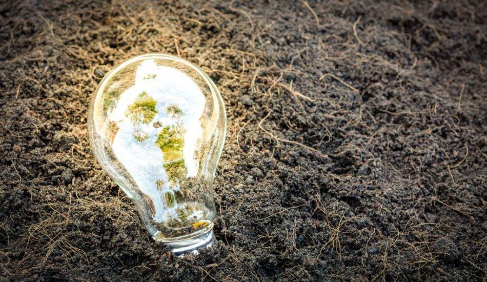 Image d'une ampoule allumée posée sur de la terre - CCI FV